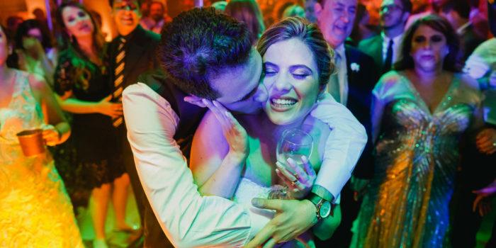 Bräutigam umarmt und küsst die Braut in einem bunten Moment